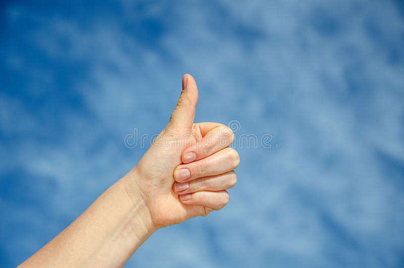 Hand with thumb on blue sky background. Ok sign by woman stock photos
