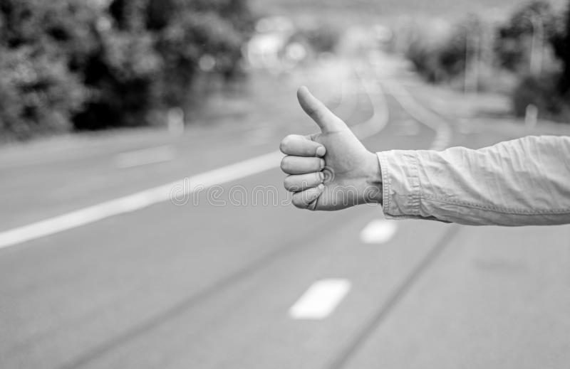 Hand thumb up gesture try stop car road background. Thumb or hand gesture hitchhiking. Make sure you know right gestures stock photography