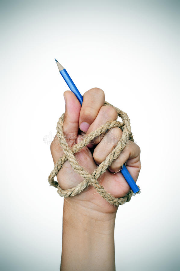 Hand tied with rope holding a pencil. The hand of a man tied with rope, holding a pencil, depicting the idea of repression of freedom of press or freedom of stock photo