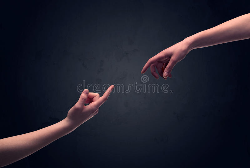 Hand about to touch another one. Two male hands reaching out to one another, almost touching, in front of dark clear empty background wall concept royalty free stock photography