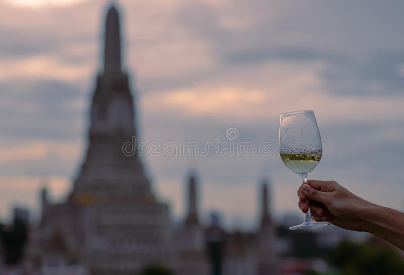 Hand toasting a glass of white wine with blurred background of temple royalty free stock images