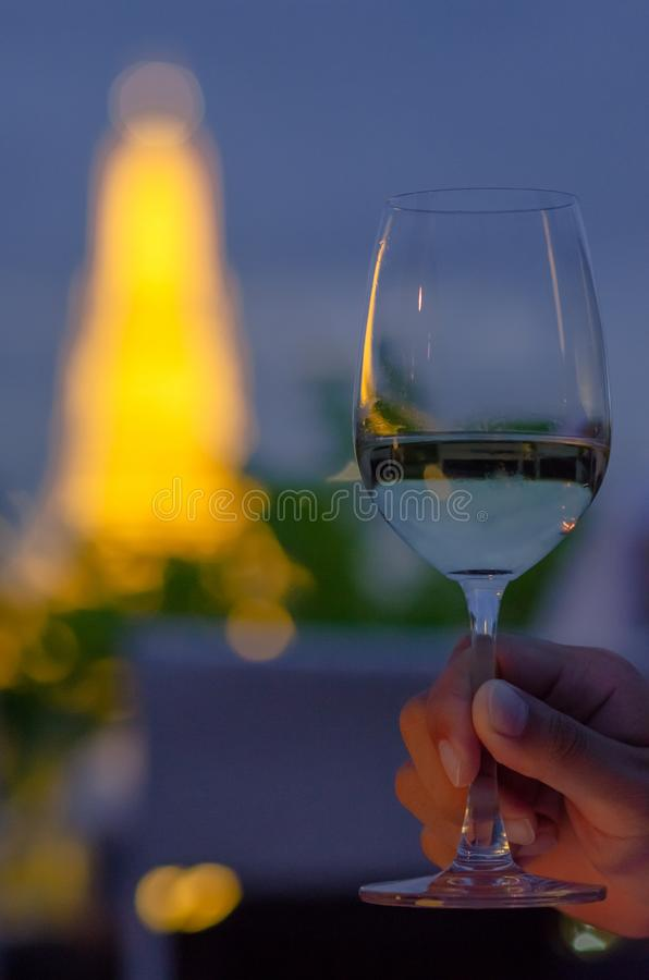 Hand toasting a glass of white wine with blurred colorful background of temple at night stock images