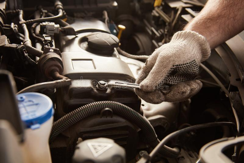 Hand with tool in the repair of car engine. Hand with tool during inspection or repair of car engine in the workshop royalty free stock photo
