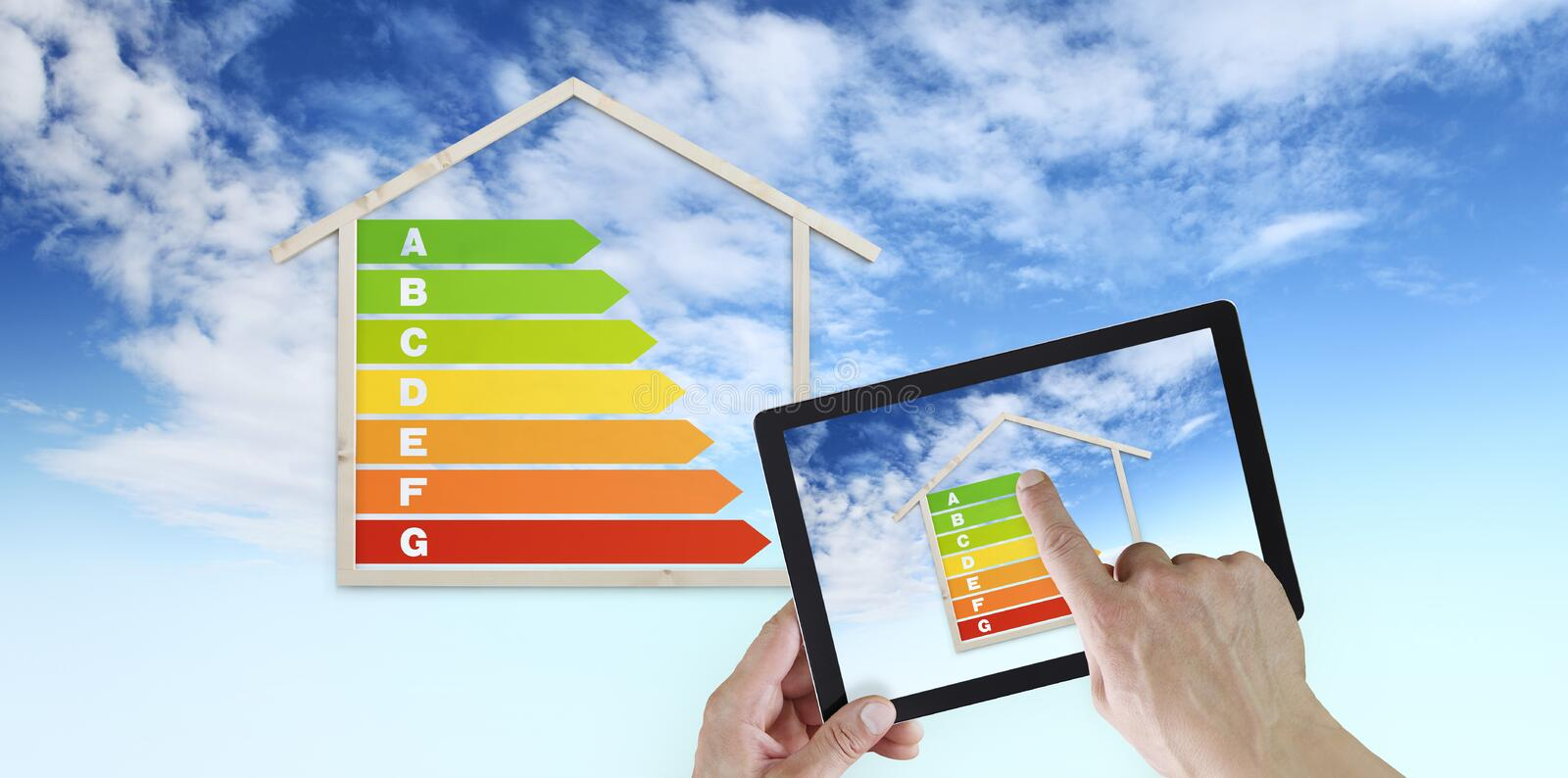 Hand touch screen of digital tablet with house shape and energy efficiency chart symbol, isolated on blu sky background, green. Buildings and save energy eco stock image