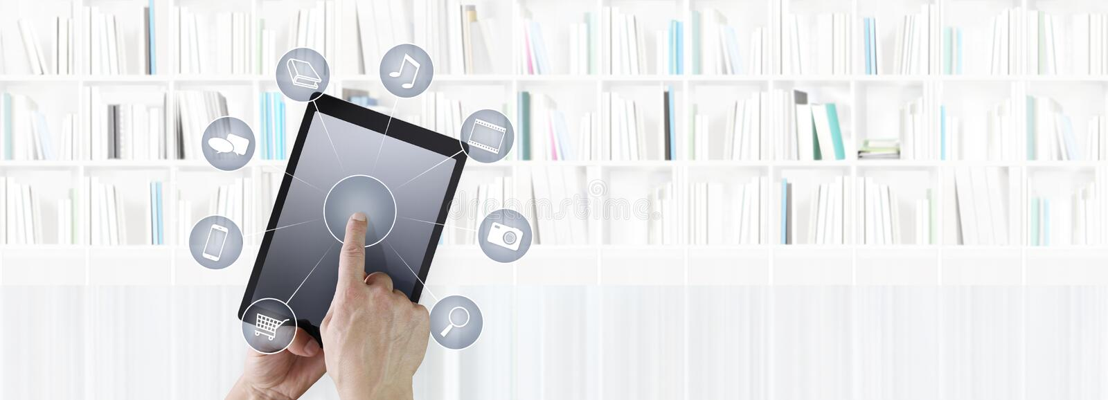 Hand touching digital tablet with icons isolated on library back. Ground stock image