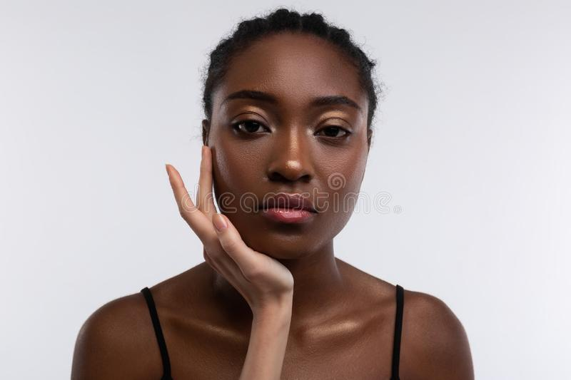 White hand touching face of dark-skinned beautiful woman royalty free stock images