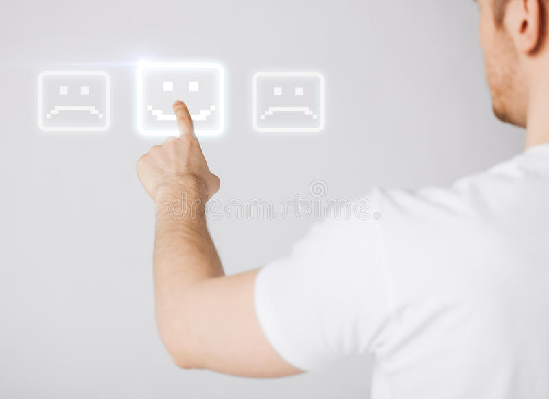 Hand touching virtual screen with smile button stock photo