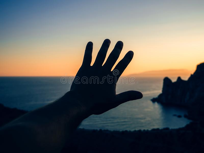 Hand of tourist at sunset on background of sea and mountains in nature. Hand of a tourist at sunset on the background of the sea and mountains in nature royalty free stock images