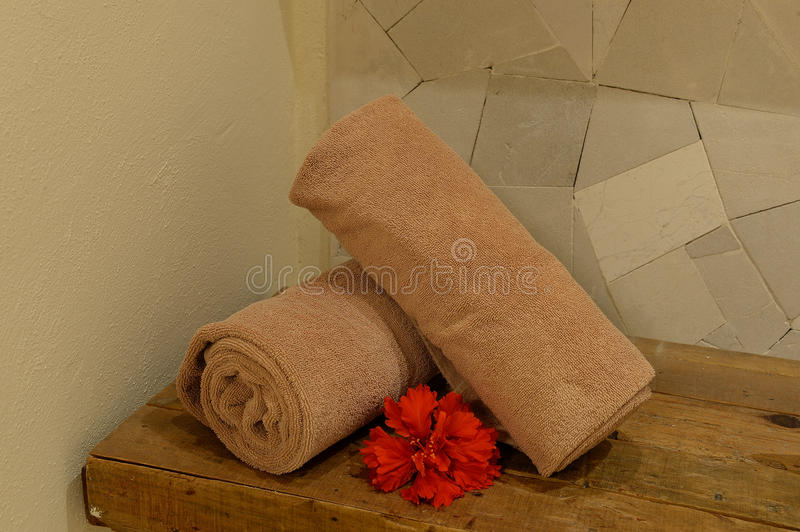 Hand towels in a health spa. Rolled hand towels next to red flowers in a health spa royalty free stock photo