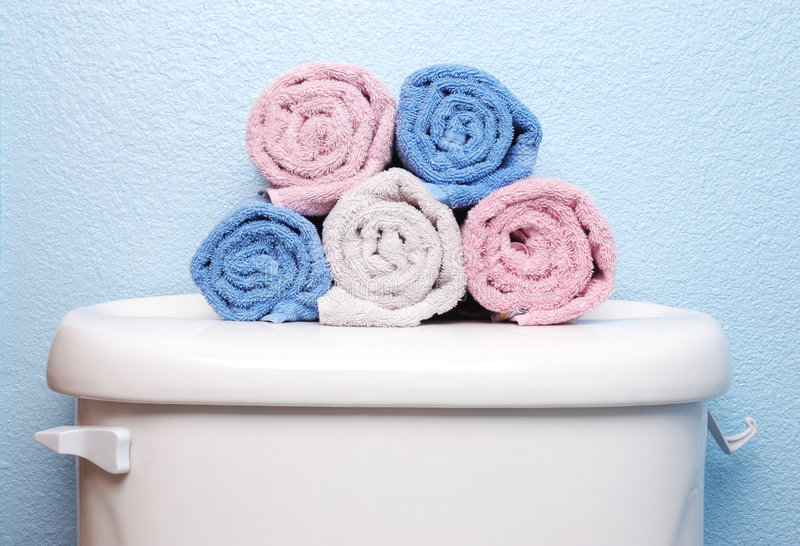 Hand Towels on Toilet Tank. Hand Towels Stacked on Toilet Tank Lid with blue wall behind stock image