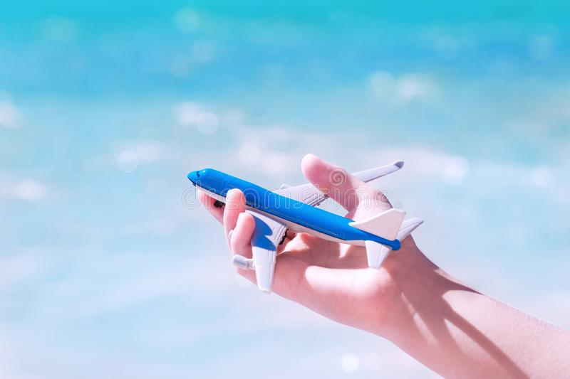 Hand with a toy aircraft against blue water and sky royalty free stock photos