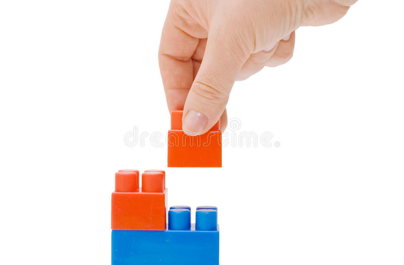 Hand with the toy block isolated. Over white royalty free stock images