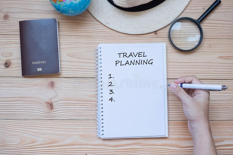 Hand traveler writing Travel planning word on notebook with accessories, Camera, Passport, Magnifying, smart Phone and hat on stock photos