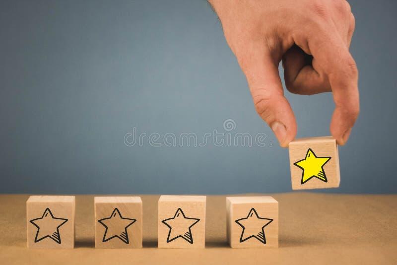 Hand trifft eine Wahl und w?hlt einen der Sterne, auf einem blauen Hintergrund lizenzfreies stockfoto