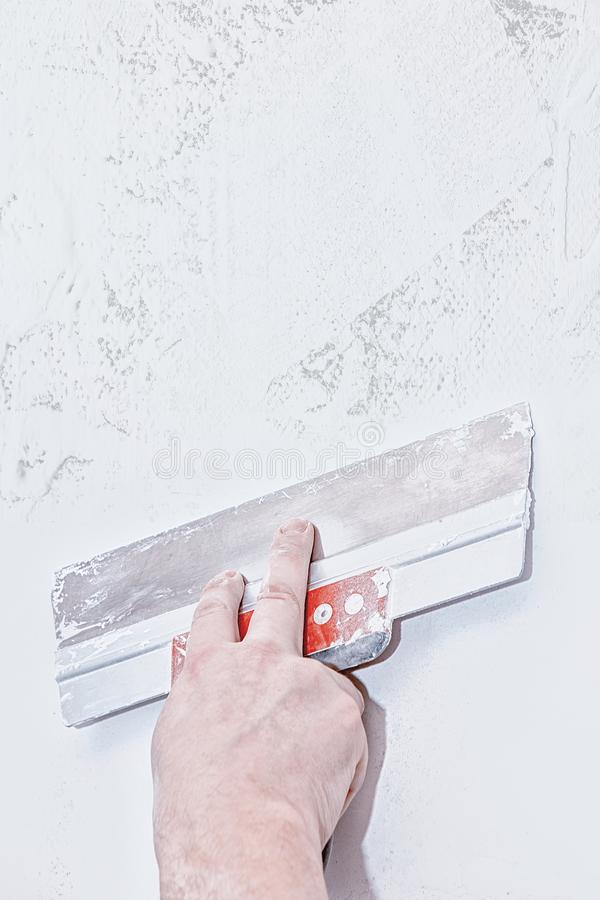 Hand with trowel, repair wall, Trowel with putty structure, the process of applying a layer of trowel, work with putty royalty free stock photography