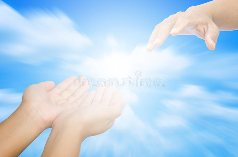Hand trying to catch up on a background of sky and light - for help. stock photos