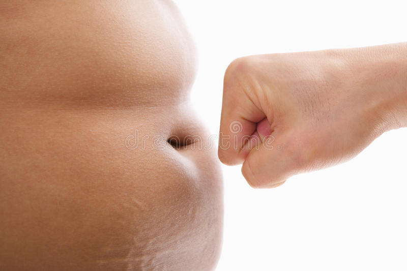 Hand Trying To Punch Fat Tummy Stock Photography