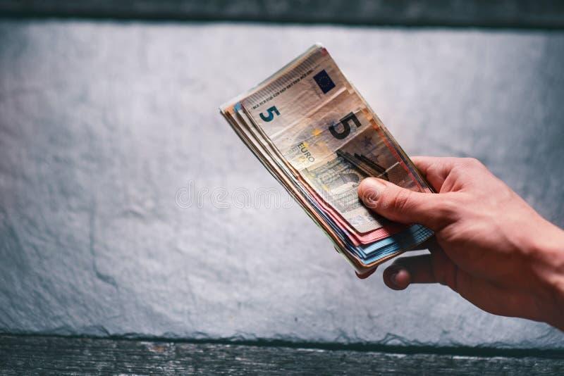 handtrzyma pieniądze młody człowiek Banknoty na kamiennym tle Euro pieniędzy banknoty różna wartość obraz royalty free