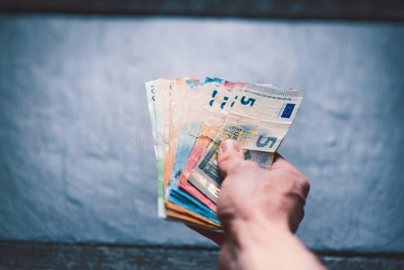 handtrzyma pieniądze młody człowiek Banknoty na kamiennym tle Euro pieniędzy banknoty różna wartość zdjęcie stock