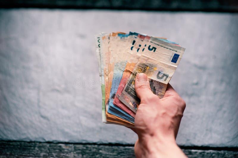 handtrzyma pieniądze młody człowiek Banknoty na kamiennym tle Euro pieniędzy banknoty różna wartość zdjęcia stock