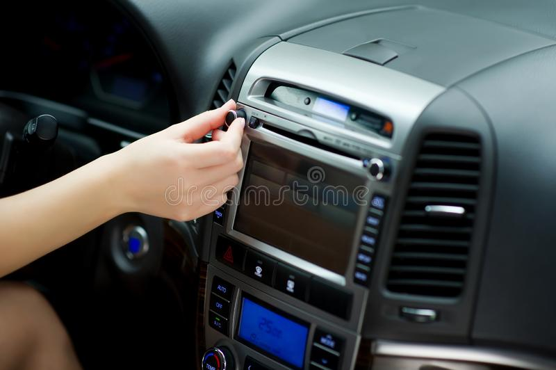 Hand tunes in radio stations and adjusting sound volume on the car audio system. Parameter settings through the on-board computer stock photo