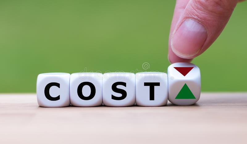 Hand is turning a dice and changes the direction of an arrow symbolizing that costs are going down . stock photo