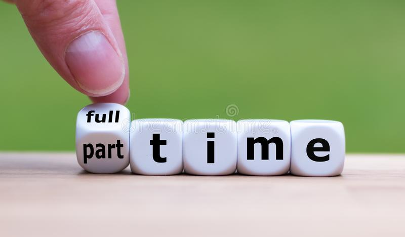 Hand is turning a dice and changes the word `full-time` to `part-time`. Or vice versa royalty free stock image