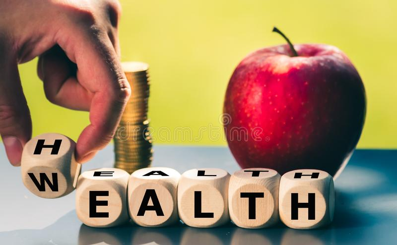 Hand is turning a dice and changes the word `health` to `wealth`. royalty free stock images