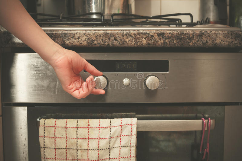 Hand turning knob on stove royalty free stock photography