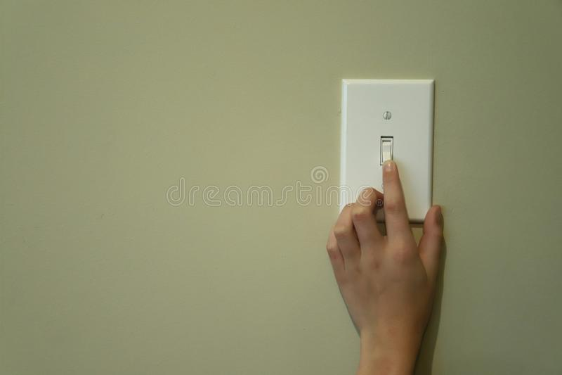 Hand turning on light switch royalty free stock photography