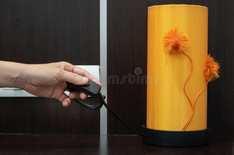 Hand turning on or off on light switch near the bed in the hotel stock photography