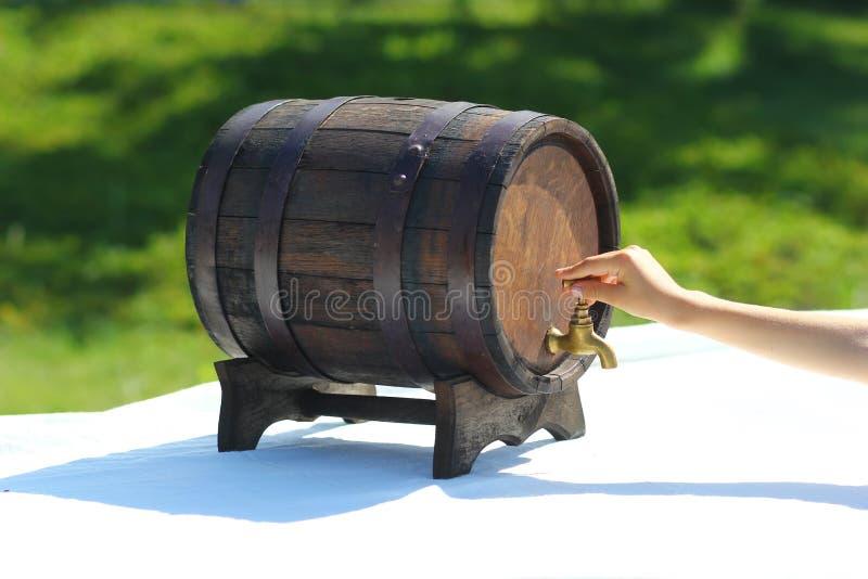 Hand turning off old kvass barrel - traditional slavic rye bread beverage stock images