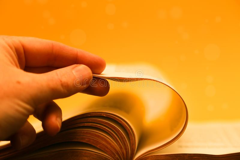 Hand turning pages of the bible - gold bible. stock image