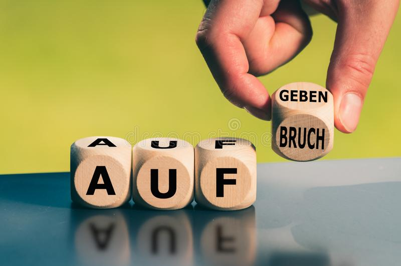 Hand turns a cube and changes the German word `Aufgeben` `give up` in English to `Aufbruch` `new beginnings` in English.  stock photo