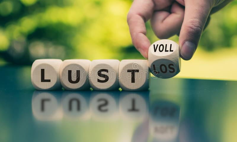 Hand turns a cube and changes the German word  `lustlos` `listless` in English to `lustvoll` `full of relish` in Englis. Hand turns a cube and changes the German royalty free stock photography