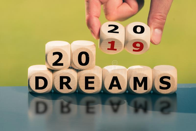 Hand turns cubes and changes the expression `2019 dreams` to `2020 dreams` stock photography