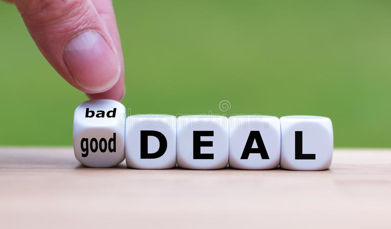 Hand turns a dice and changes the expression `bad deal` to `good deal`. Hand turns a dice and changes the expression `bad deal` to `good deal royalty free stock photography