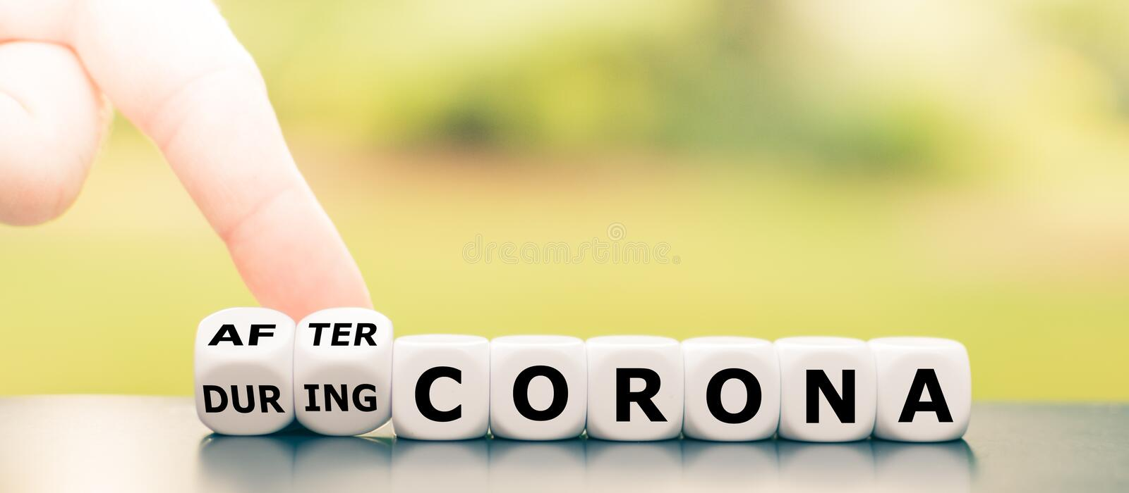 Hand turns dice and changes the expression `during Corona` to `after Corona`. Hand turns dice and changes the expression `during Corona` to `after Corona stock image
