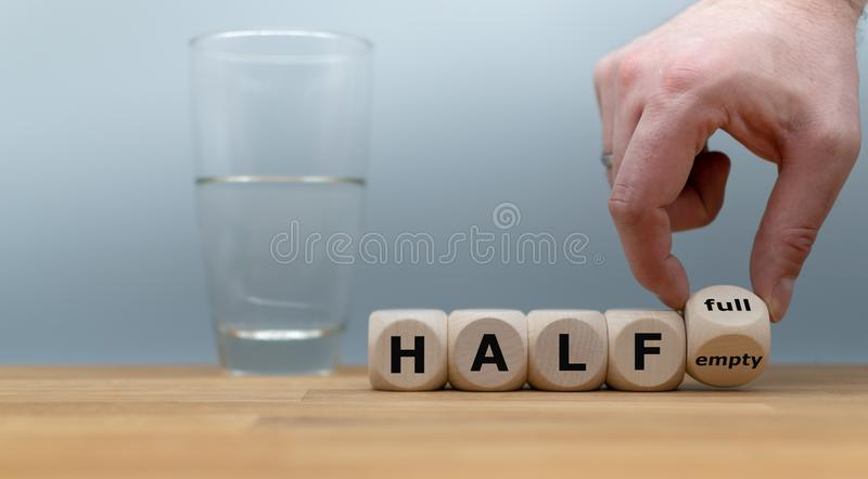 Hand turns a dice and changes the expression `half empty` to `half full`. stock photography