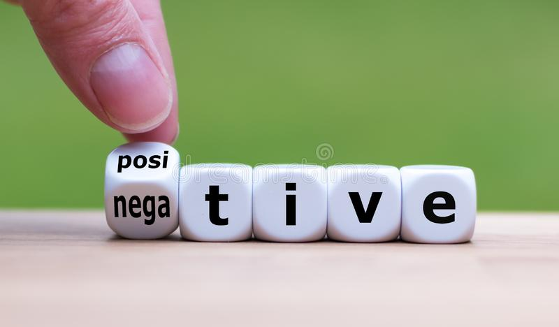Hand turns a dice and changes the expression `negative` to `positive`. royalty free stock photo