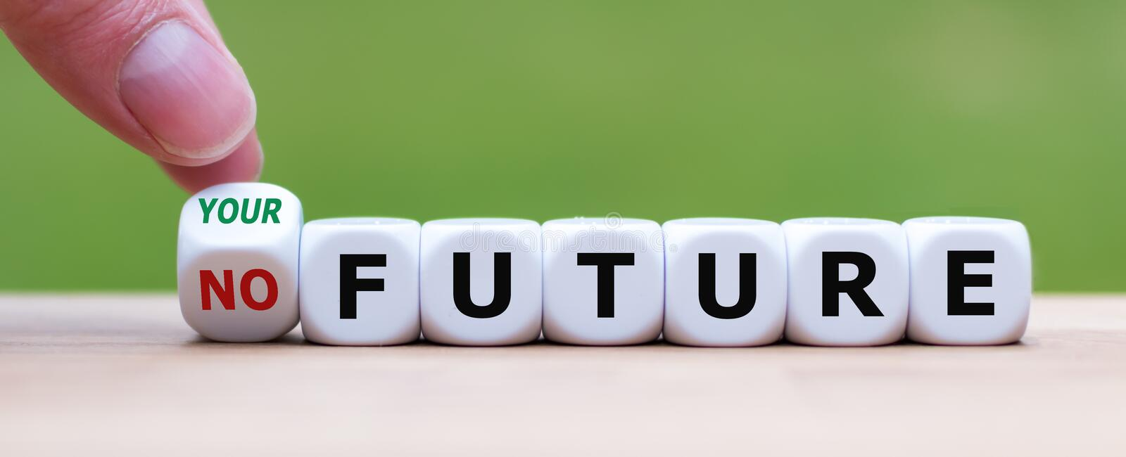 Hand turns a dice and changes the expression `no future` to `your future`. royalty free stock photo