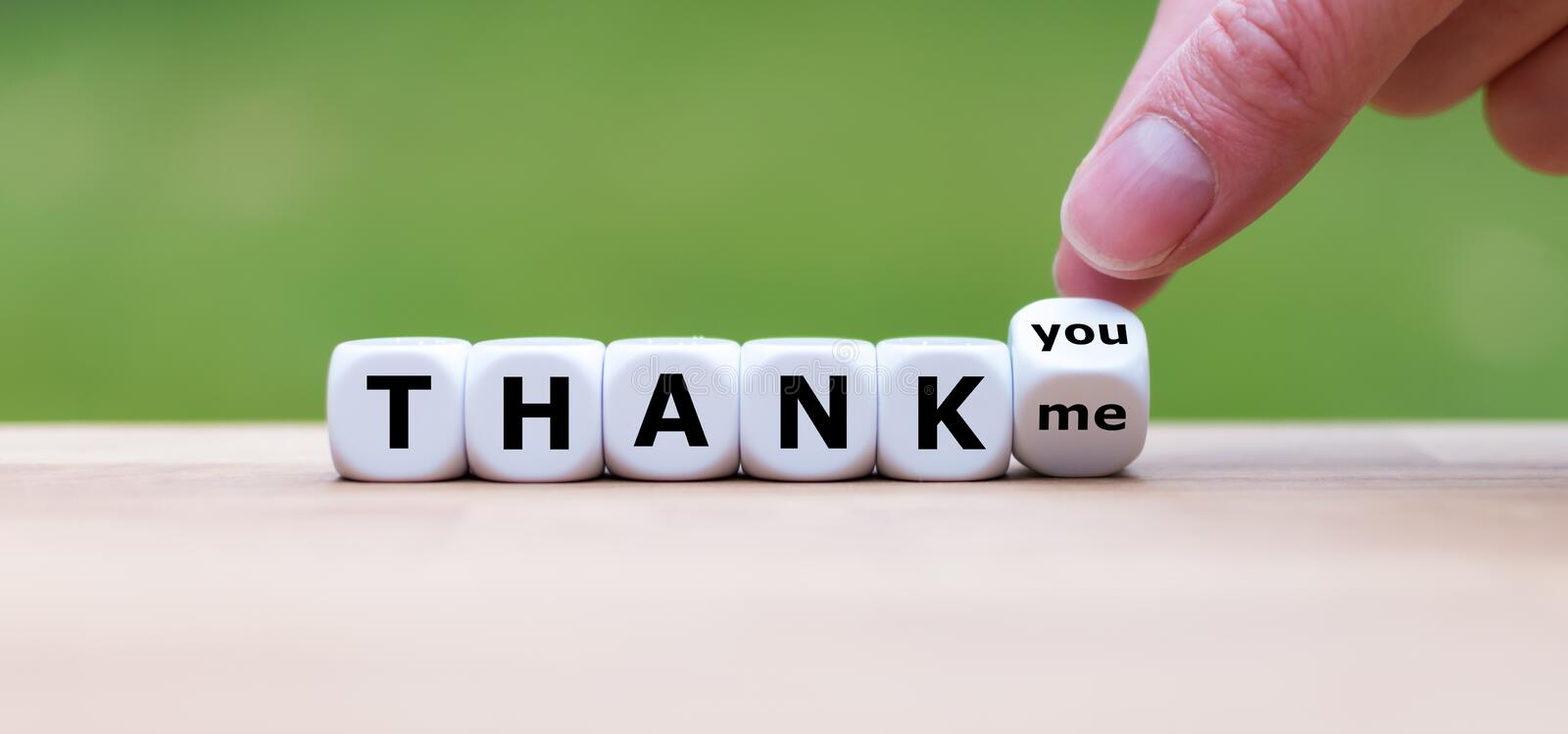 Hand turns a dice and changes the expression `THANK ME`` to `THANK YOU`. stock photography