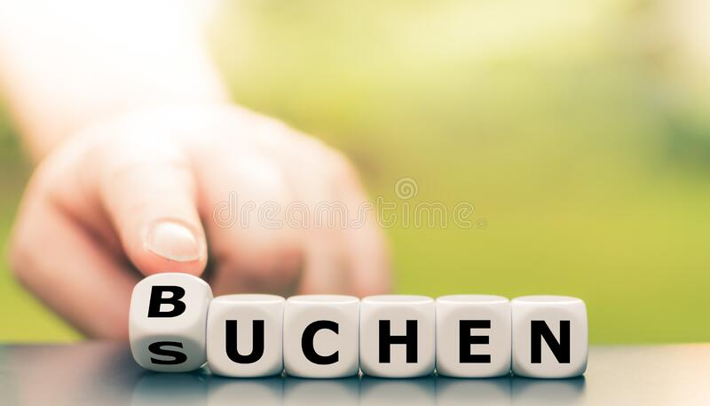 Hand turns a dice and changes the German word `suchen` `search` in English to `buchen` booking` in English. Hand turns a dice and changes the German word ` royalty free stock photography
