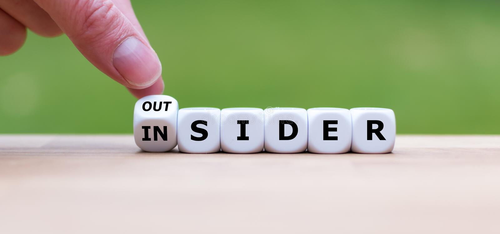 Hand turns a dice and changes the word `OUTSIDER` to `INSIDER` stock images