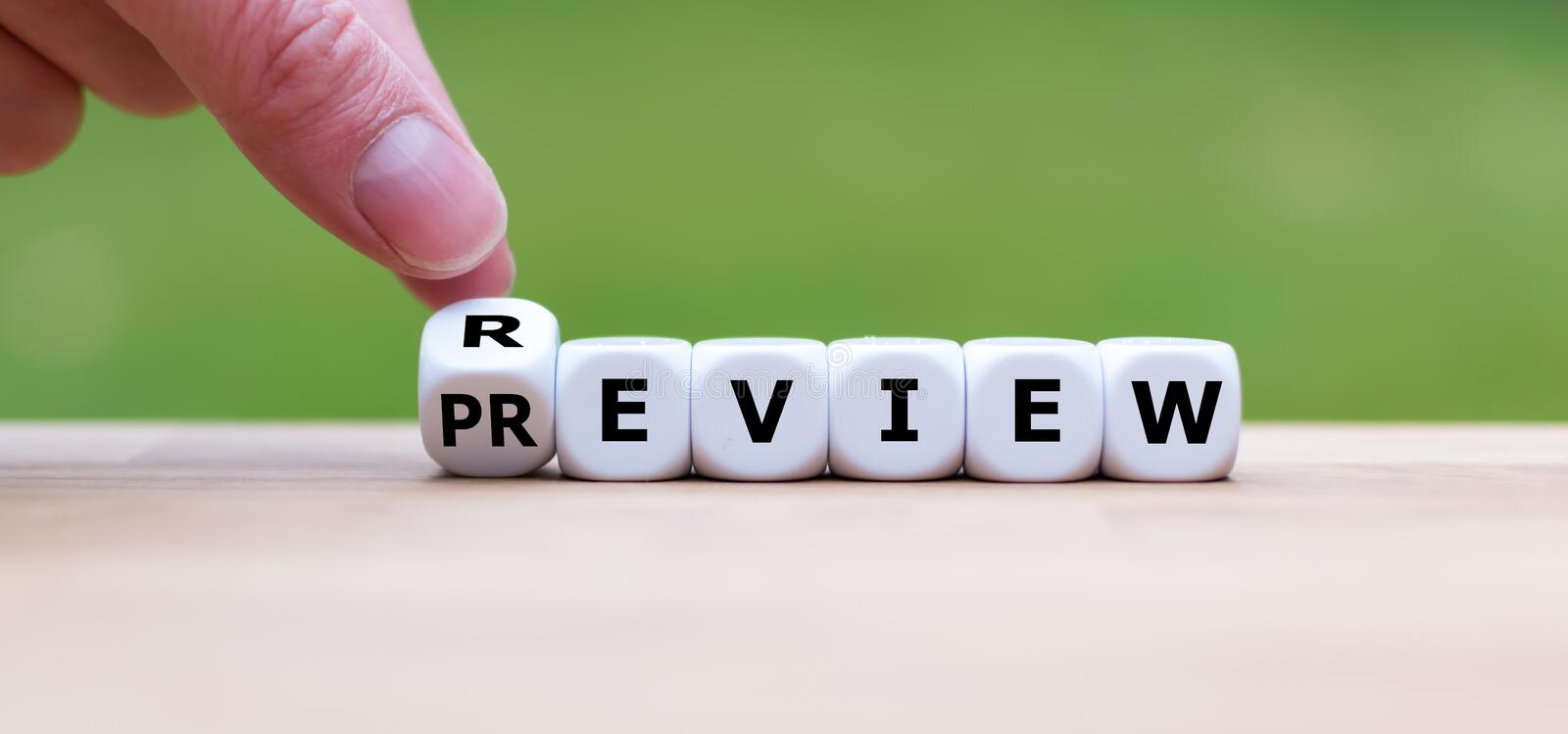 Hand turns a dice and changes the word `review` to `preview`. Hand turns a dice and changes the word `PREVIEW` to `REVIEW` or vice versa royalty free stock photos