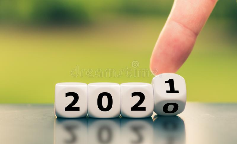 Hand turns a dice and changes the year `2020` to `2021`. Hand turns a dice and changes the year `2020` to `2021 royalty free stock photos