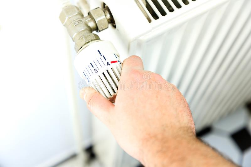Hand turns on the heating stock image