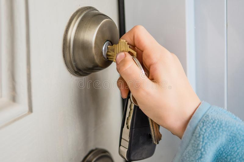 Hand turns the key in the door lock royalty free stock image