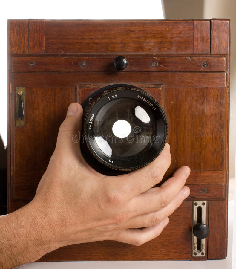 Hand turns the lens. Of the old wooden camera stock photos