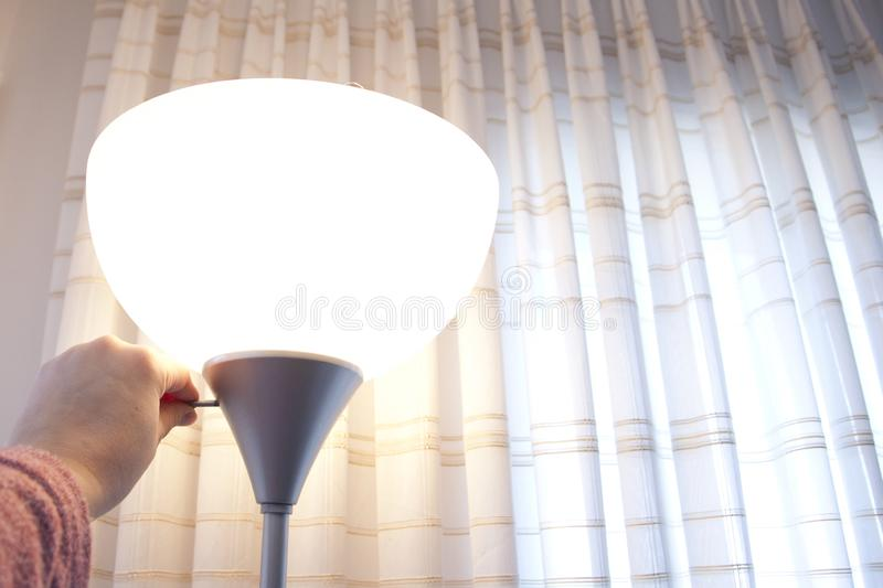 Turning on a lamp at home stock image